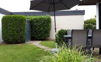 Sonnige Terrasse mit Sonnenschirm und Sitzgruppe